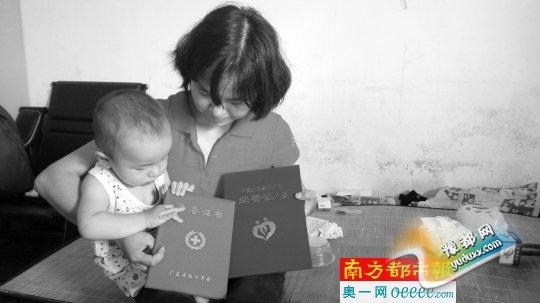 苏先进的妻子夏银菊向记者出示捐献器官的荣誉证书。