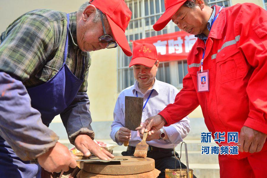 年轻的志愿者郝强等人拜80岁的曹志林为师学习磨刀技艺。仝江摄