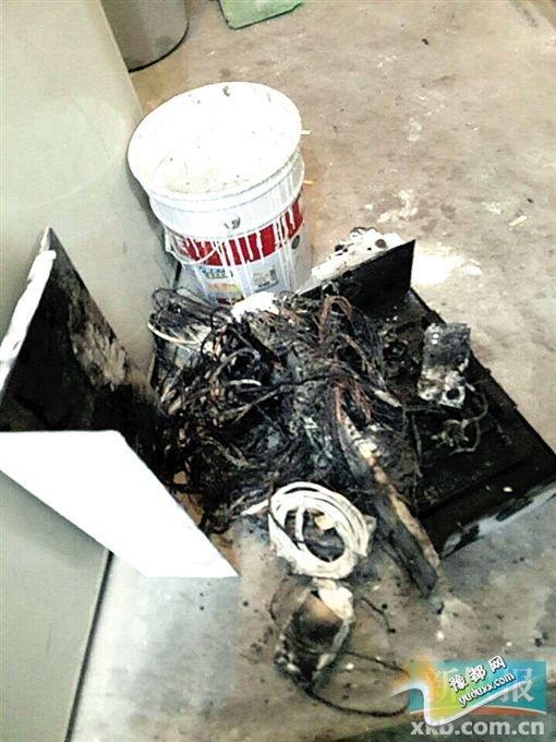 维修工从电梯顶部拆下已烧得面目全非的电路板,是这次事故的元凶。 谢先生供图