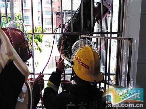 救援人员探身出窗解救小孩。(视频截图)