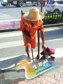 10日,邓贤国在清扫路面垃圾。