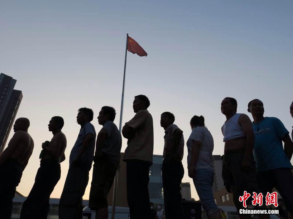 8月13日傍晚,泰达二中安置点市民排队领餐。 中新社发 石岩 摄