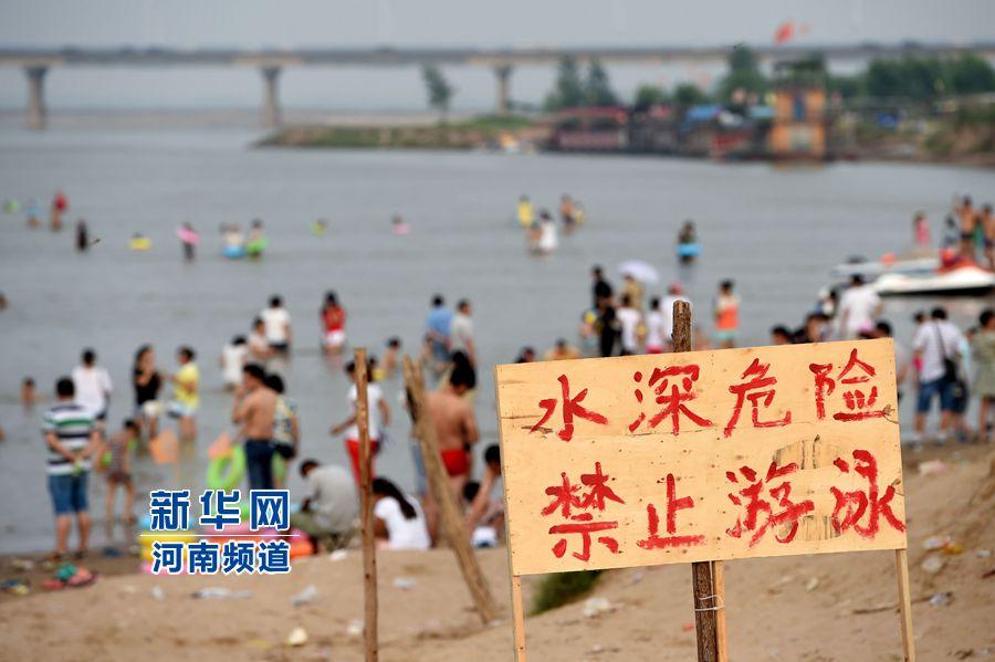 """8月13日,在郑州黄河花园口游览区内,市民在立有""""禁止游泳""""警示牌河段下水游泳。"""