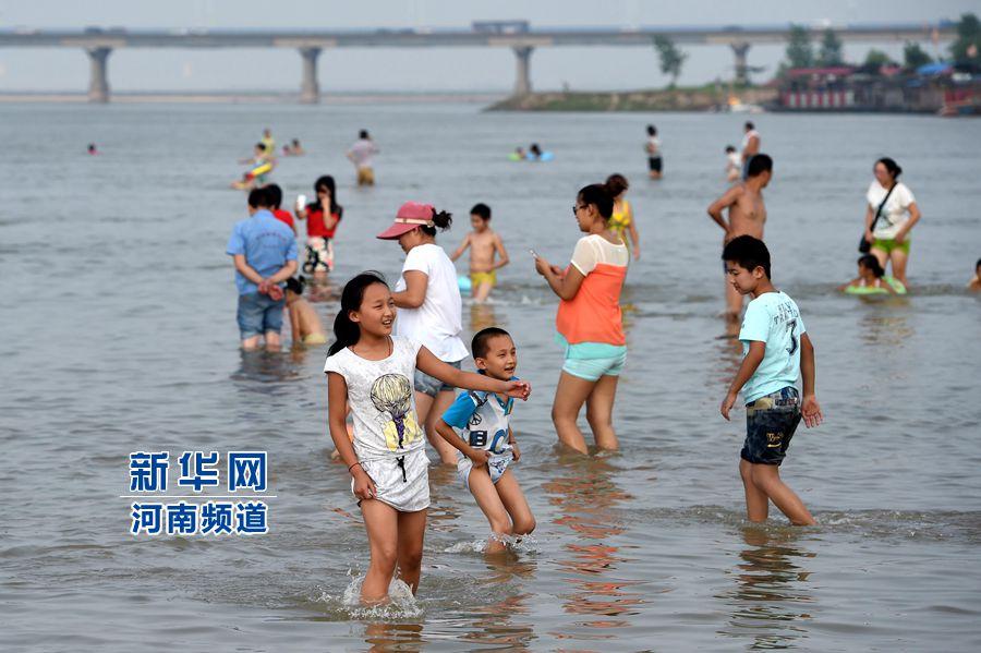 8月13日,市民带着孩子在黄河花园口段游泳嬉戏。新华社记者 李博 摄