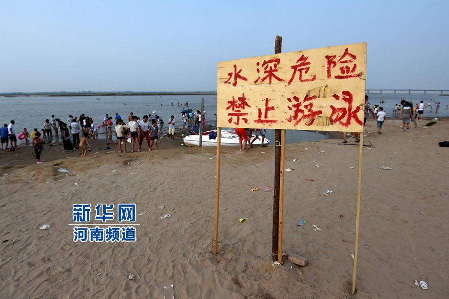 """8月13日,在郑州黄河花园口游览区内,河岸边树立有""""禁止游泳""""的警示牌,但仍有许多市民下水游泳。新华社记者 李博摄"""