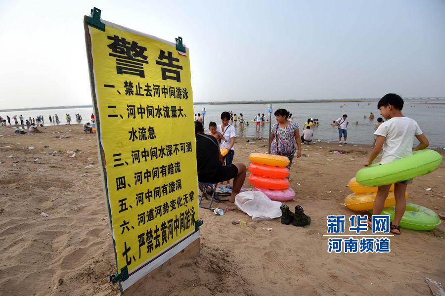 8月13日,在郑州黄河花园口游览区内,河岸边树立有警示牌,但仍有许多市民下水游泳。