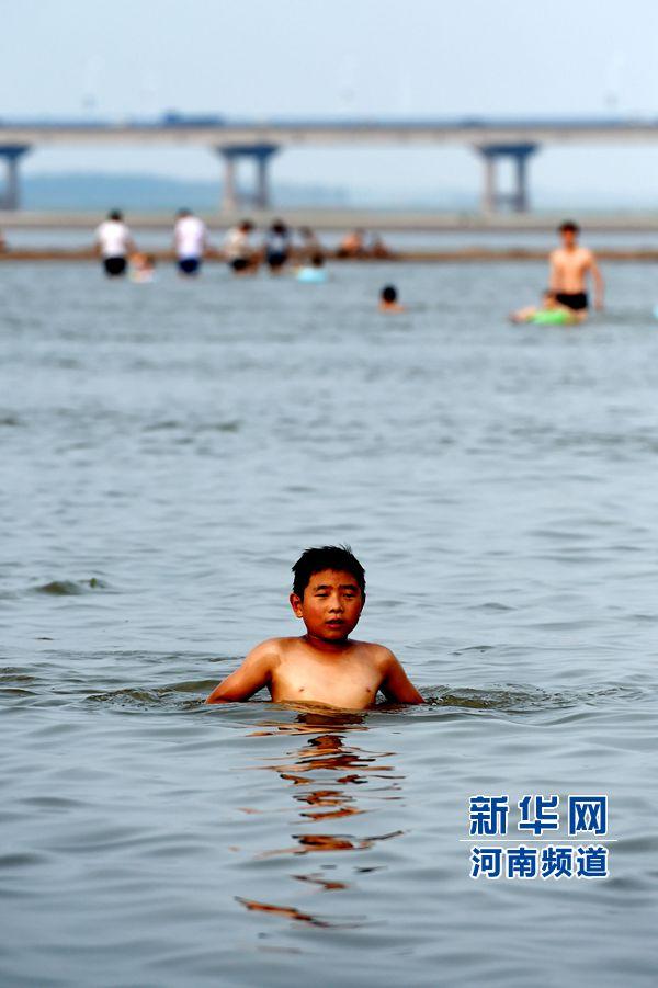 8月13日,一位小朋友在在黄河花园口段游泳嬉戏。