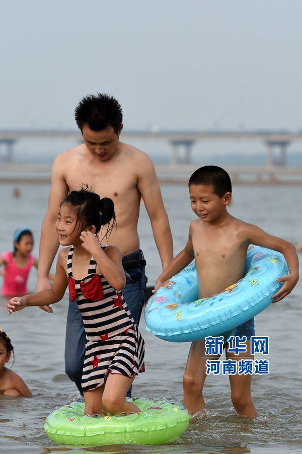 8月13日,市民带着孩子在黄河花园口段游泳嬉戏。新华社记者 赵鹏 摄