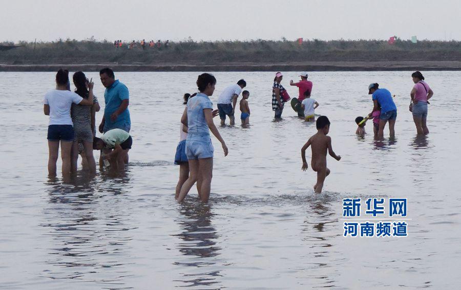 市民带着孩子在黄河花园口段游泳嬉戏(8月9日摄)。新华社记者 赵鹏 摄