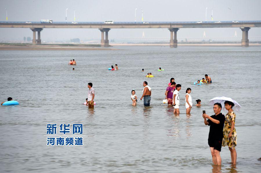 8月13日,市民带着孩子在黄河花园口段游泳嬉戏。新华社记者李博 摄