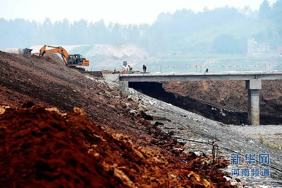 8月18日,工作人员和大型机械在出山店水库施工现场作业。