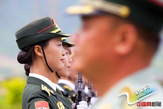 2015年8月14日,北京某阅兵训练基地,一名军官从正在为抗战胜利70周年阅兵式训练的三军仪仗队女兵身前走过。中国网记者 吴闻达 摄