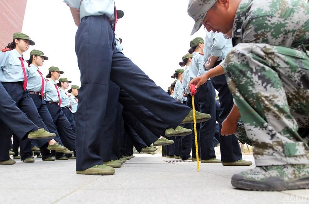"""""""以前上初中和高中都进行过军训,但像这样每一个动作都有硬性指标的还是第一次,难度确实大。顶着瓶子的时候,开始还好,后来稍不留神瓶子就容易掉下来。""""一位新生说。图为2015年9月17日,郑州航院的""""准空姐""""们正在军训,踢正步卷尺测量。"""