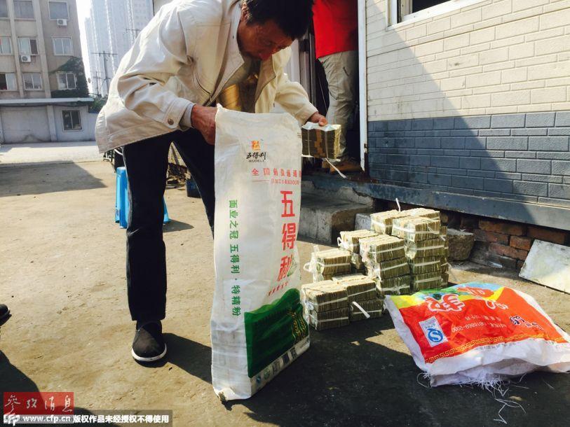 在清点完毕后,他们又将钱装回编织袋,并进行了封口,记者用一只手拎起编织袋,感觉非常的沉重,每个袋子差不多能达到20斤左右。
