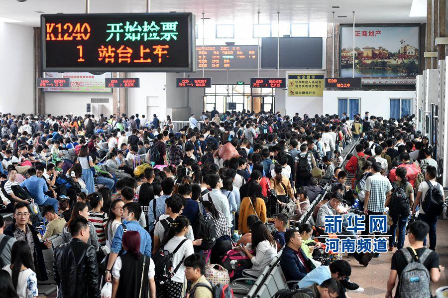 9月30日,旅客在郑州火车站候车大厅内排队准备进站乘车。