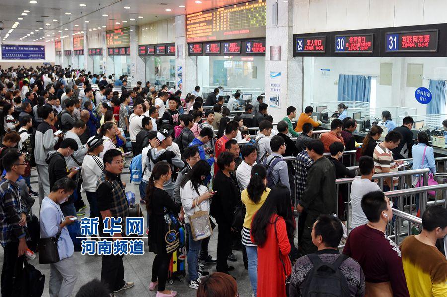 9月30日,旅客在郑州火车站售票大厅内排队购票。