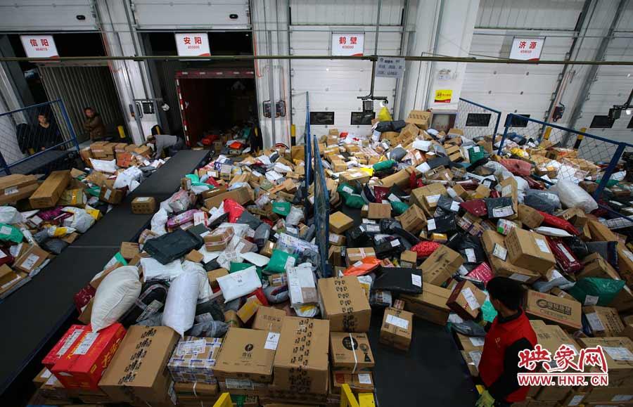 一位工人分拣着快递包裹,在门口的货车司机则等待装好后出发