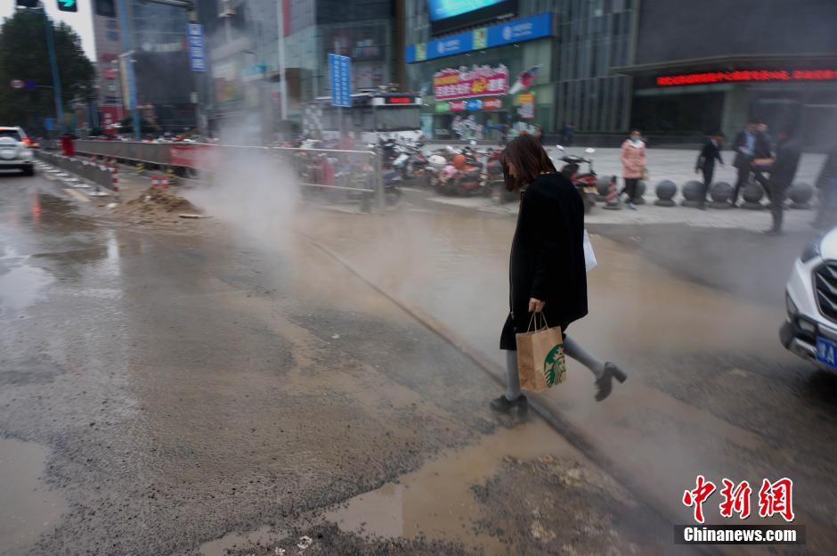 """11月18日,位于郑州市花园路与农业路口的一处热力管道爆裂,路口热气腾腾、地面直往外冒热水,蔓延到马路上形成积水一滩,大量行人、车辆经过此处犹如""""腾云驾雾过险滩""""。中新社记者 王中举 摄"""