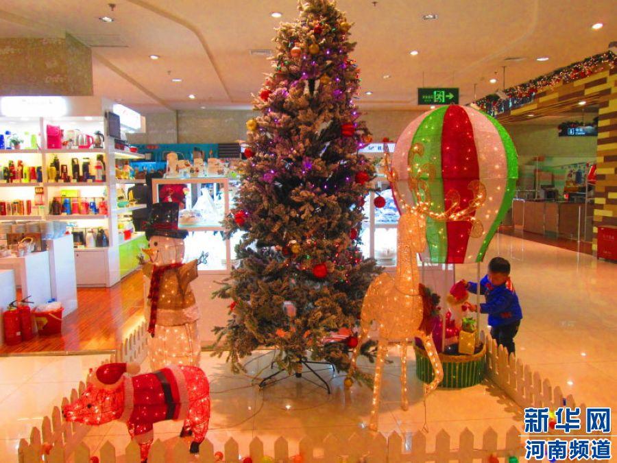 郑东新区CBD丹尼斯七天地:小朋友在圣诞树旁开心的玩耍