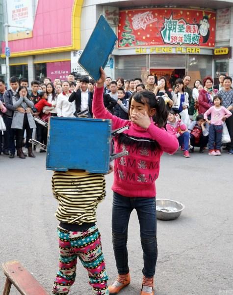 2016年02月12日,广西壮族自治区南宁市新华街,女孩在街上表演变法无头魔术。唐辉吉 摄/视觉中国