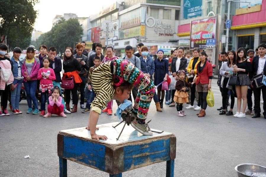 2016年02月12日,广西壮族自治区南宁市新华街,女孩在四方桌上表演柔功。唐辉吉 摄/视觉中国
