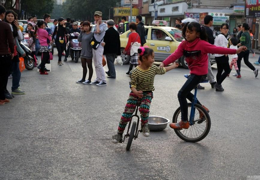 2016年02月12日,广西壮族自治区南宁市新华街,女孩在街上表演独轮车拾碗。唐辉吉 摄/视觉中国
