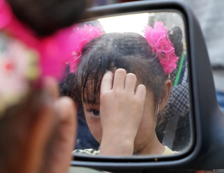2016年02月12日,广西壮族自治区南宁市新华街,女孩表演前到城管车边的后视镜装扮。