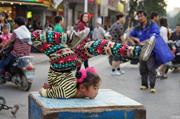 俩河南女孩春节广西卖艺耍杂技 引众人围观