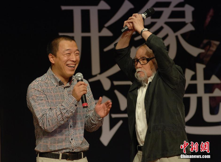 """2009年7月15日,""""我心中的经典电影形象""""--新中国成立六十周年大型电影经典形象评选活动在北京正式启动,葛存壮即兴演绎自己在电影《小兵张嘎》中塑造的经典形象――龟田小队长,青年演员黄渤与之""""搭戏""""。 中新社发"""