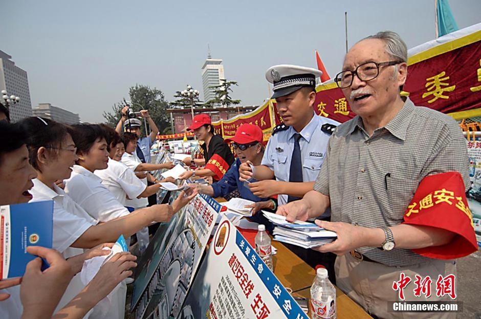 """2005年9月8日,著名电影表演艺术家葛存壮戴上红色""""交通安全员""""袖标,和交警一起向群众发放宣传品,宣传《交通法》。"""