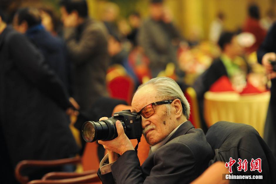 2012年1月17日,首都文化界新春招待会在北京举行,北京书画、诗曲、演艺届百余知名人士在新春佳节来临之际欢聚一堂。图为老电影艺术家葛存壮先生在招待会上专心拍照片。