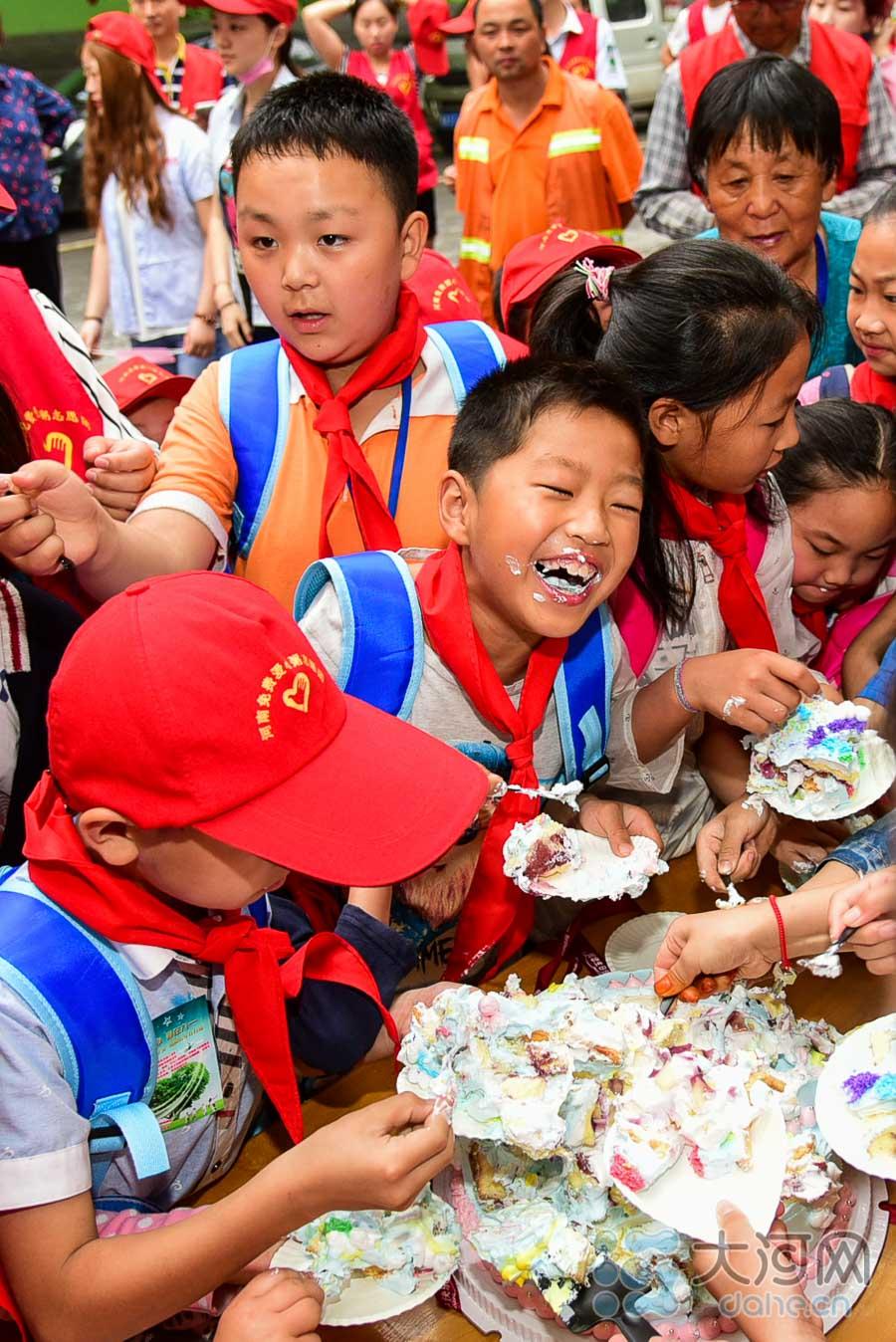 爱心志愿者和孩子们围成一团,切蛋糕、分蛋糕,孩子们开心的笑了。蛋糕吃的满脸都是,大家连声祝福孩子们节日快乐。
