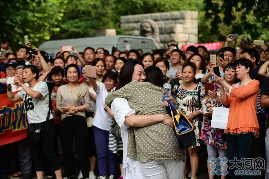 走出考场的考生和自己的家人抱在一起。