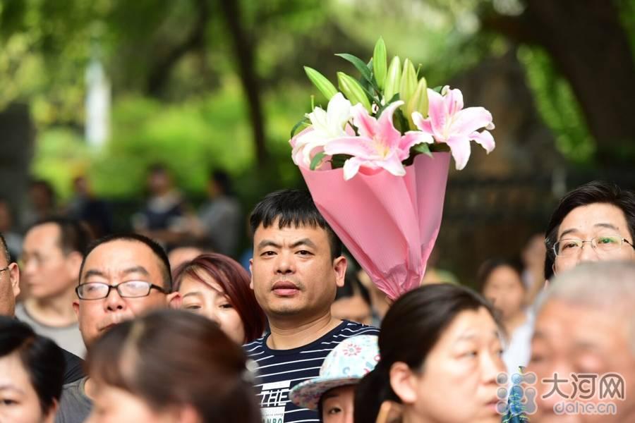 6月8日下午,2016年高考圆满落幕。今年,河南共82万学子走进考场同场竞技,向心中的大学梦发起冲刺。 上图:一位考生家长手举鲜花,等待自己的孩子。