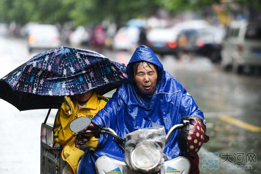 冒雨接孙子回家的老人。
