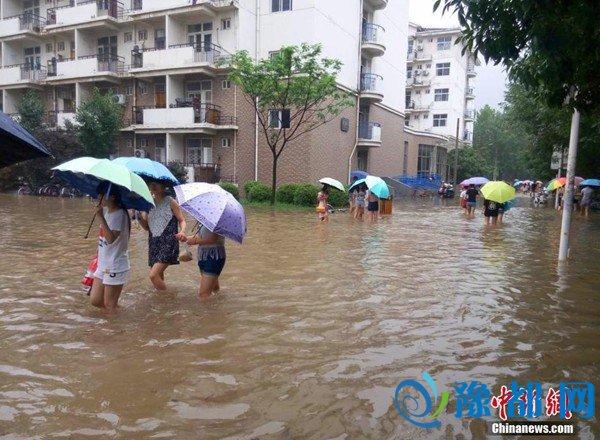 """7月9日,河南师范大学校园内,学生卷起裤腿在水中穿行,该校校园内部分路段积水严重,操场变身""""泳池"""",校园商铺被淹。(查看多图)"""