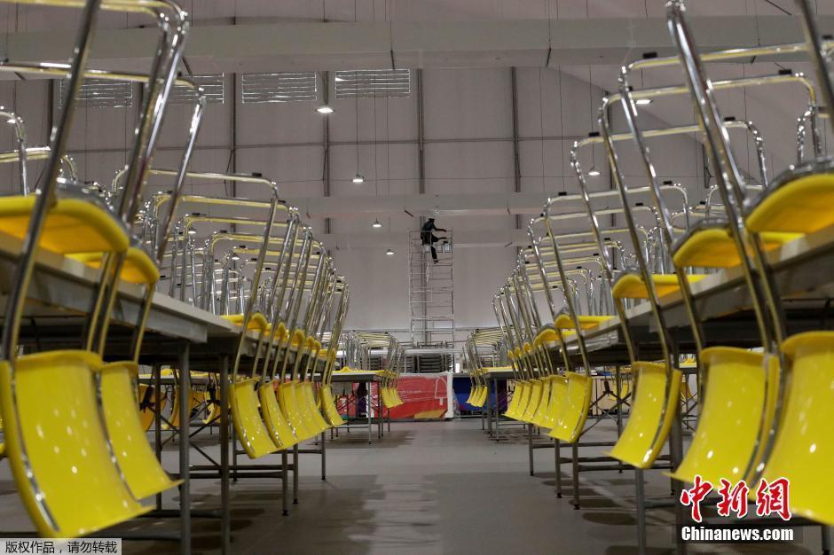 当地时间7月23日,巴西里约热内卢,这个由新建的高层住宅构成的社区将成为近11000名里约奥运会参赛运动员以及约6000名教练等其他工作人员吃饭、睡觉以及训练的固定区域。图为奥运村内的食堂内一名工作人员正在粉刷屋顶。