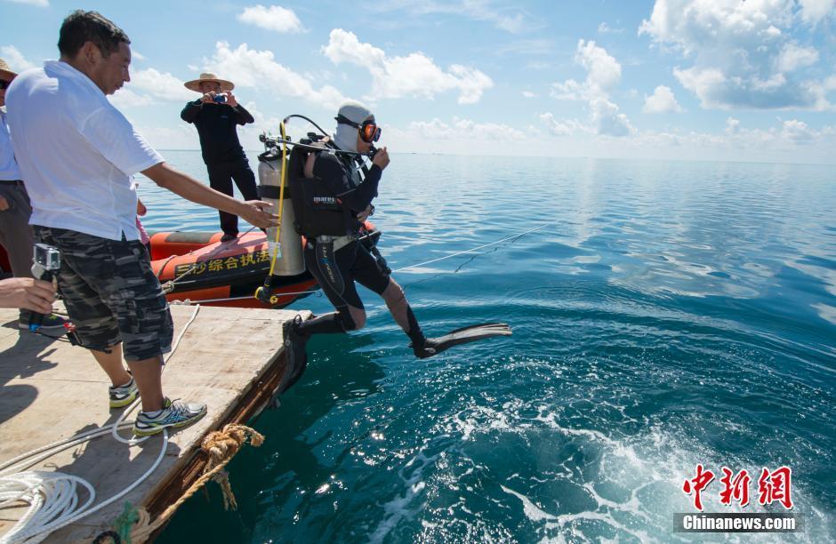 """7月24日,经过专家的现场探查确认,三沙市政府正式命名西沙群岛永乐环礁的海洋蓝洞为""""三沙永乐龙洞""""(Sansha Yongle Blue Hole),其被证实为世界已知最深的海洋蓝洞。据介绍,""""三沙永乐龙洞""""位于三沙市西沙群岛永乐环礁晋卿岛与石屿的礁盘中,深达300.89米,地址坐标为北纬16°31′30″、东经111°46′05″。经过探查,西沙永乐蓝洞基本为垂直洞穴,蓝洞口径为130米,洞底直径约36米,尚未观测到蓝洞内与外海联通,洞内水体无明显流动。图为远眺龙洞。中新社记者 骆云飞 摄"""