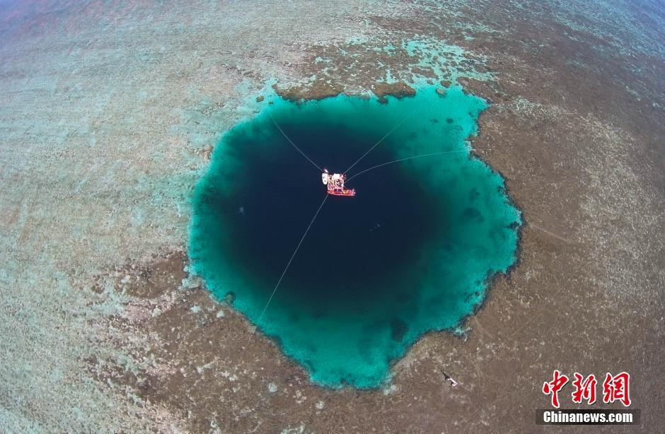 """7月24日,经过专家的现场探查确认,三沙市政府正式命名西沙群岛永乐环礁的海洋蓝洞为""""三沙永乐龙洞""""(Sansha Yongle Blue Hole),其被证实为世界已知最深的海洋蓝洞。据介绍,""""三沙永乐龙洞""""位于三沙市西沙群岛永乐环礁晋卿岛与石屿的礁盘中,深达300.89米,地址坐标为北纬16°31′30″、东经111°46′05″。经过探查,西沙永乐蓝洞基本为垂直洞穴,蓝洞口径为130米,洞底直径约36米,尚未观测到蓝洞内与外海联通,洞内水体无明显流动。图为龙洞航拍图片。中新社记者 骆云飞 摄"""