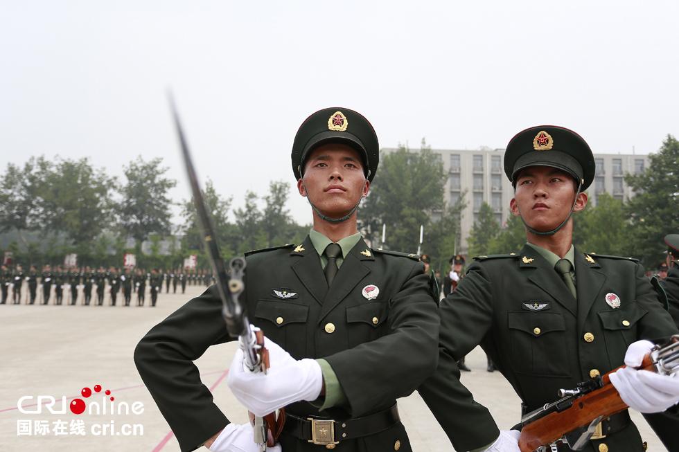 天气炎热,仪仗兵的脸颊布满汗水,他们没有丝毫懈怠,认真完成每一个训练动作。摄影:沈��
