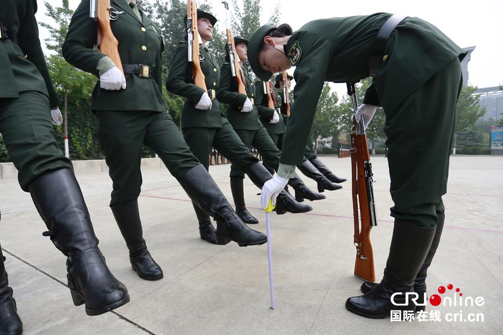 教官正在用卷尺测量踢正步时脚离地的高度。摄影:沈��