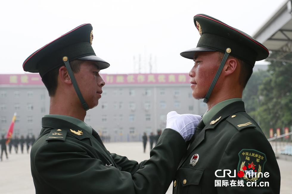训练间隙,仪仗兵相互整理军装。摄影:沈��