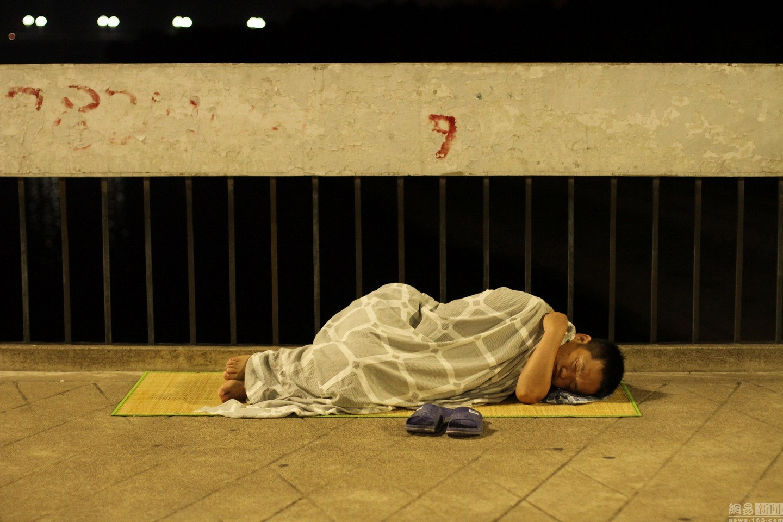 图为夜宿街头的洛阳瓜农。