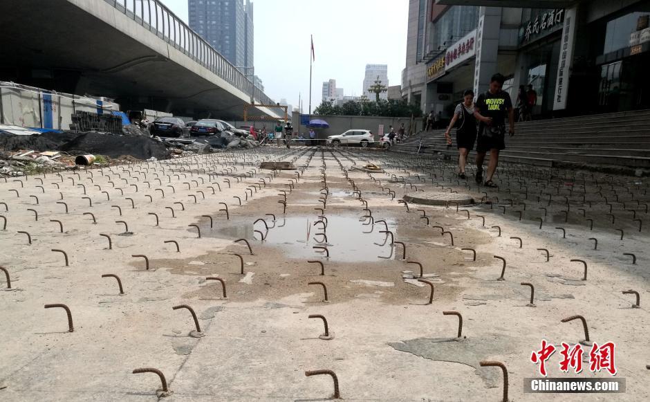 """8月10日,河南郑州,位于农业路、花园路附近的豫博大厦写字楼前广场,布满密密麻麻的钢勾。连日来,豫博大厦前广场路面上突然""""长""""出了密密麻麻、眼花缭乱的弯曲钢勾。记者经调查了解,当地为了农业路快速通道项目,将该广场规划成了一条行车通道。因此处广场下方系大厦的两层地下停车库,钢勾则是为了下一步的道路加固所用。此举引发大厦业主及在此办公的员工强烈不满。他们在吐槽出行不便的同时,更为下一步道路一旦通行后路面是否安全深感担忧。图为大厦广场上密密麻麻的钢勾给行人进出造成极大不便。刘鹏 摄"""