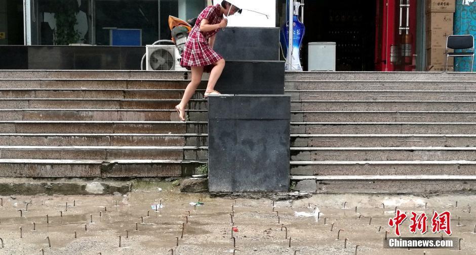 8月10日,河南郑州,位于农业路、花园路附近的豫博大厦写字楼前广场,布满密密麻麻的钢勾。图为一名在此大厦办公的员工跳上台阶躲避钢勾。刘鹏 摄
