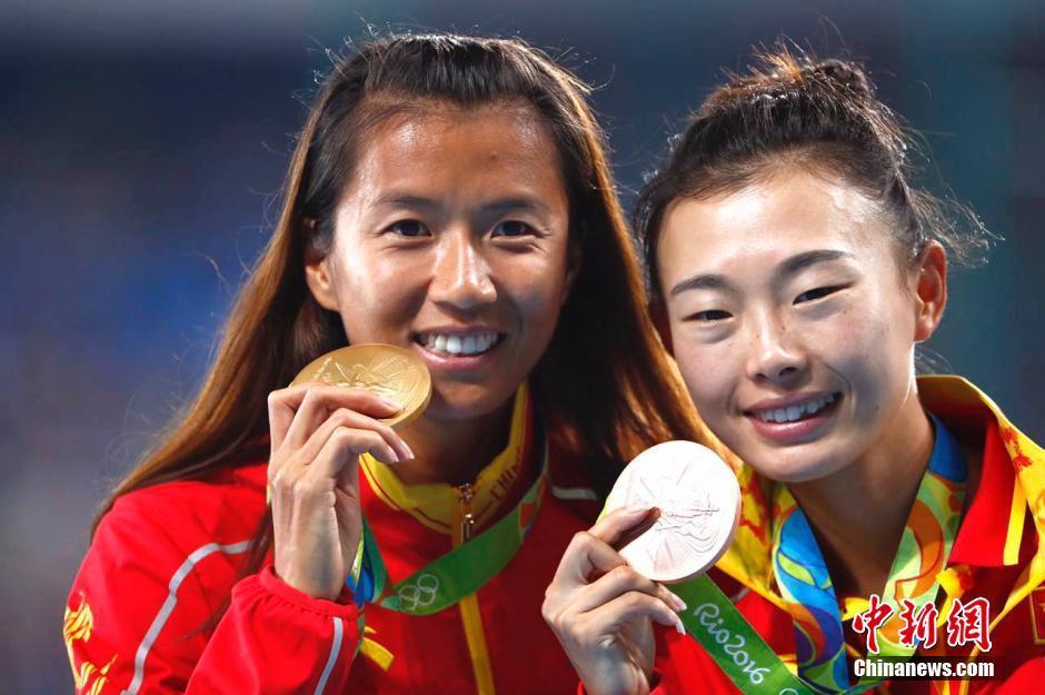 当地时间8月19日,里约奥运女子20公里竞走决赛,中国选手刘虹(左)以1小时28分35秒摘取金牌,墨西哥选手冈萨雷斯获得银牌,吕秀芝(右)获得铜牌,另一位中国选手切阳什姐名列第五。图为刘虹与吕秀芝合影。中新网记者 富田 摄