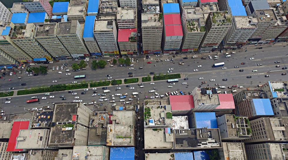 2016年8月24日,河南郑州,即将开拆的郑州市最大城中村陈寨。从空中看陈寨,楼房栉比鳞次,大部分楼房房顶,全部是蓝色或红色的彩钢瓦。