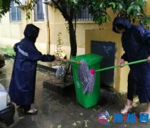 西园街志愿者冒雨用雨水刷洗垃圾桶和路面
