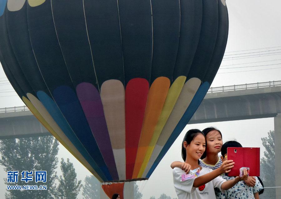 9月15日,五彩斑斓的热气球在洛阳市八里唐艺术公园上空飘浮。 当日,在河南省洛阳市八里唐艺术公园内举行的国际热气球旅游节正式开幕,各色各样的热气球吸引众多市民和游客前来体验游玩,欢度中秋小长假。 新华社记者李安摄