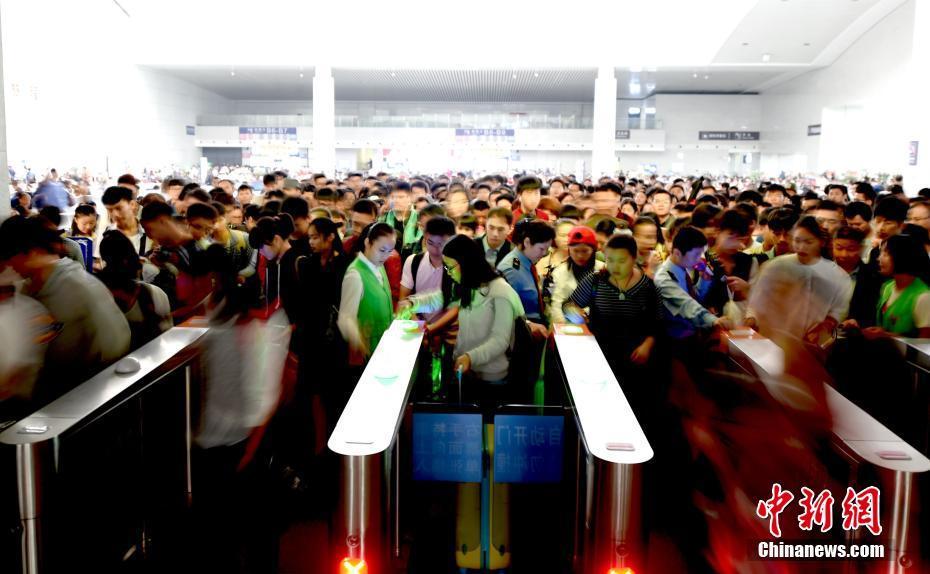 """9月30日,南昌火车站工作人员引导旅客通过检票闸机进站。""""十一""""国庆假期来临,中国铁路迎来旅客出行高峰。中新社记者 鲍赣生 摄"""